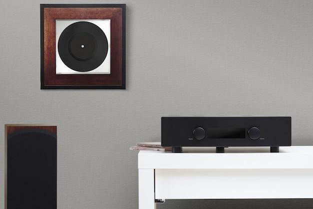 Hifi system amplifier and floor acoustics. framed vinyl on the wall.
