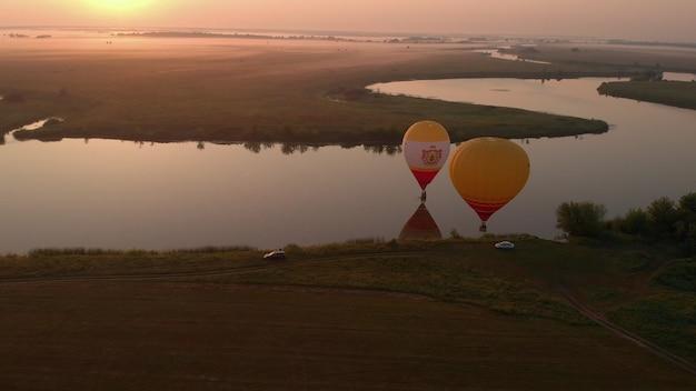 高高度空中ドローンの広い視野。 2021年7月18日、ロシアのリャザンで朝、熱気球のコレクションが澄んだ青い空を飛んでいます。