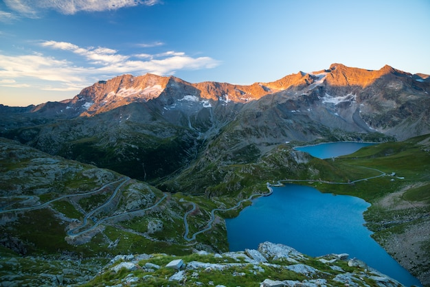 High altitude alpine lake, dams and water basins in idyllic land with majestic rocky mountain peaks glowing at sunset