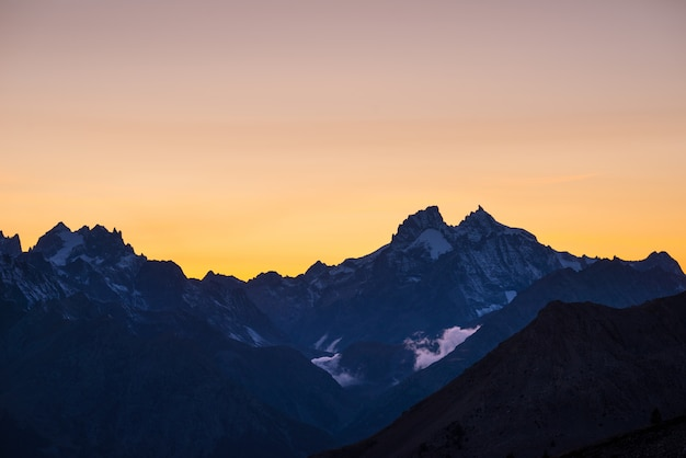 High altitude alpine landscape at dawn with first light glowing the majestic high peak of the barre des ecrins
