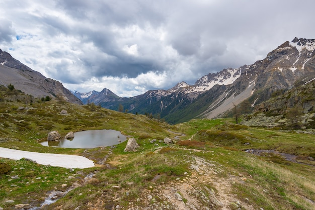 High altitude alpine pond in rocky landscape. dramatic stormy sky and snowcapped mountain range