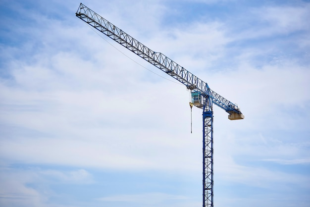 A high-altitude crane against a cloudy blue sky.