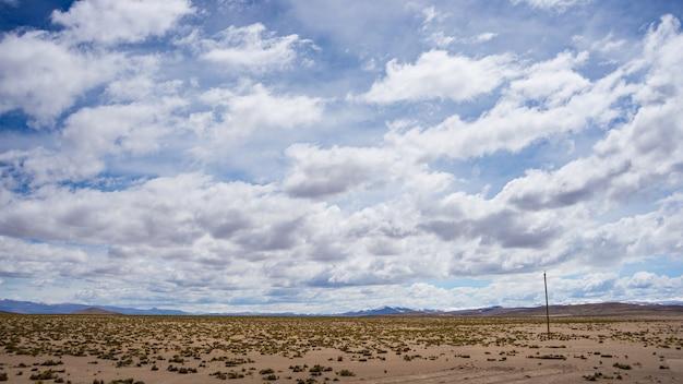 風光明媚な劇的な空と厳しい不毛の風景の中の高高度の流れるストリーム。ペルーアンデス高地の4000 mで上から広角ビュー。