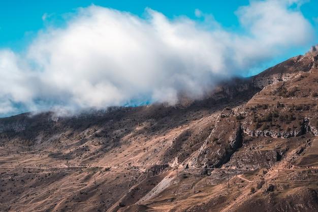山の上の大きな白い雲のある高地の風景。