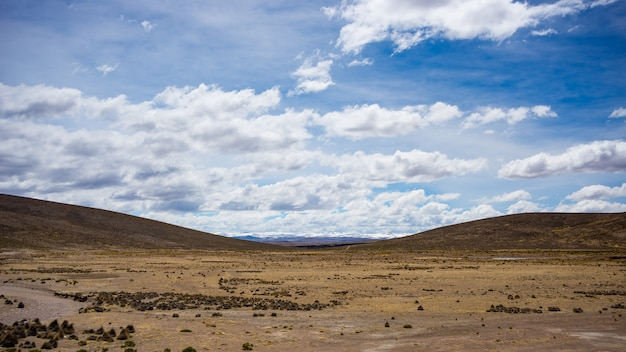 High altitude landscape with harsh barren landscape and scenic dramatic sky. wide angle view from above at 4000 m on the andean highlands, peru.