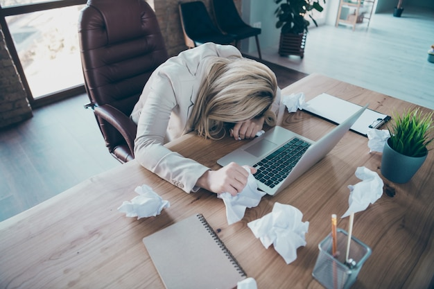 Высокий угол обзора фотографии головы бизнес-леди, лежащей на столе, усталой