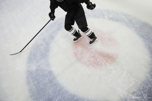 Выстрел под высоким углом хоккеиста, бегущего по льду на стадионе