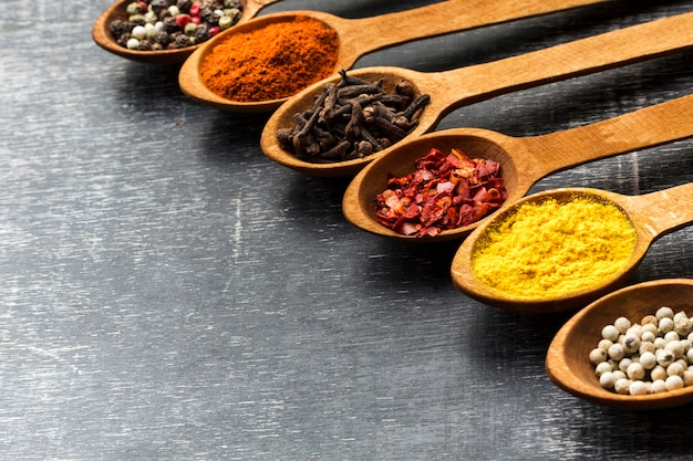 High angle aligned spoons with spices powder