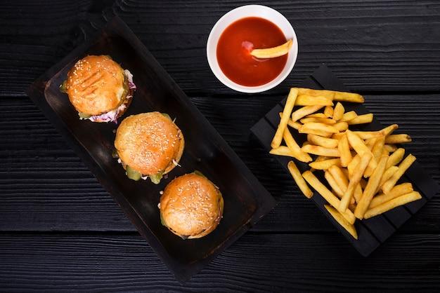 Высокий угол американских гамбургеров с картофелем фри и соусом