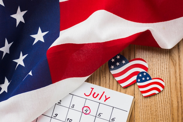 High angle of american flags and calendar on wooden surface