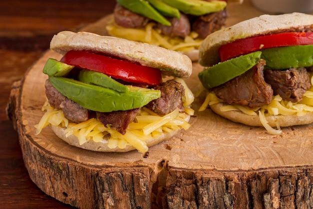 Alto angolo di arepas con avocado e carne su tavola di legno