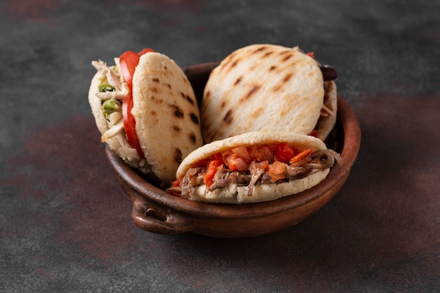High angle arepas with meat and tomatoes