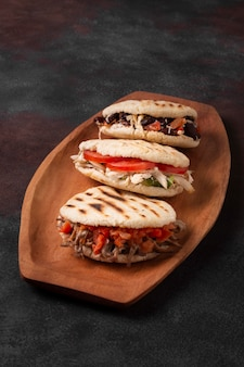 High angle arepas on wooden tray
