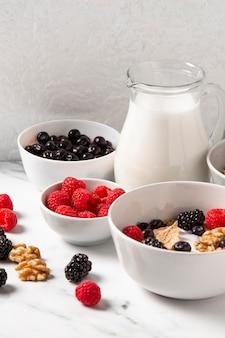 Disposizione ad alto angolo di cereali sani ciotola con frutti di bosco
