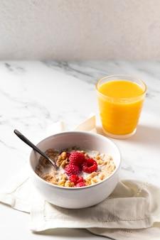 Disposizione ad alto angolo di cereali sani ciotola con succo d'arancia