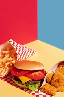 High angle arrangement with delicious fast food on yellow background