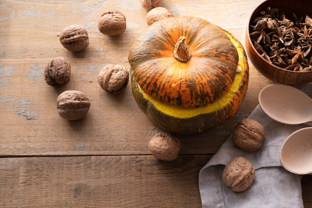 High angle arrangement with pumpkin and nuts on wooden background