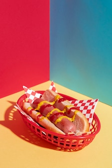 Композиция под большим углом с вкусным хот-догом и корзиной
