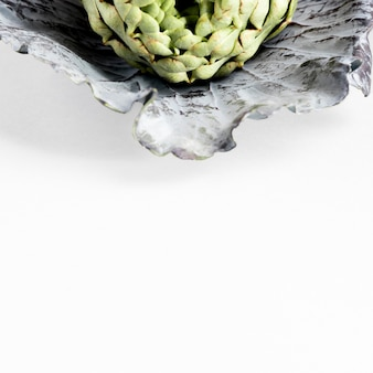 High angle of artichoke on cabbage leaf