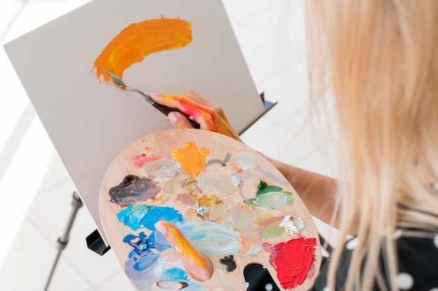 High angle of artist painting while holding paint palette