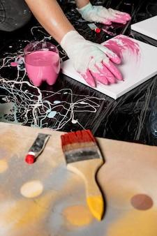 Alto angolo di pittura dell'artista con pennello e colore