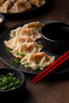 Alto angolo di piatto asiatico sulla piastra con erbe e bacchette