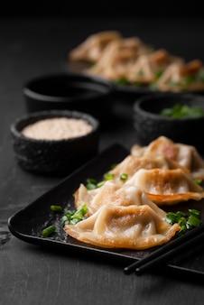 Alto angolo di piatto asiatico sulla piastra con erbe aromatiche