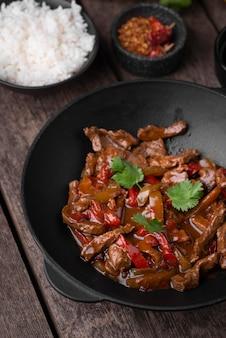 Alto angolo di piatto asiatico sulla piastra con carne e riso