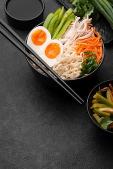 Alto angolo di piatto asiatico con uova e copia spazio