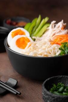 Alto angolo di piatto asiatico con uova e insalata in una ciotola