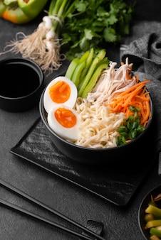 Alto angolo di piatto asiatico con uova e insalata