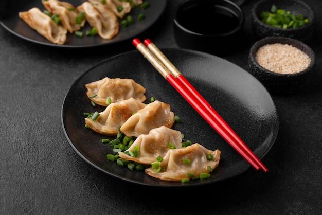 Alto angolo di piatto di gnocchi asiatici con erbe e bacchette
