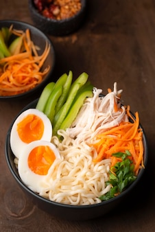 High angle of asian noodles with eggs and variety of vegetables
