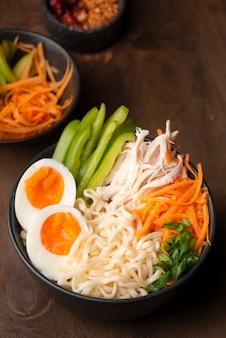Alto angolo di tagliatelle asiatiche con uova e varietà di verdure