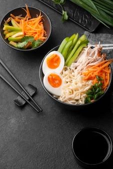 Alto angolo di tagliatelle asiatiche con uova e verdure