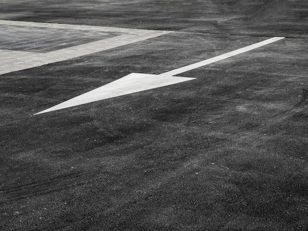 High angle of asphalt with white arrow