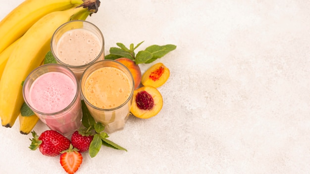 High angle of assortment of fruit milkshakes in glasses with copy space