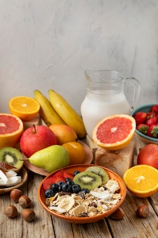 High angle of assortment of fruits with breakfast cereals and milk