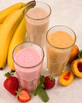 High angle of assortment of milkshakes with bananas and strawberries