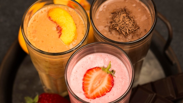 High angle of assortment of milkshakes with chocolate and strawberry