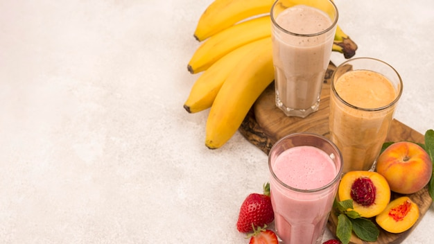 High angle of assortment of milkshakes with fruits and copy space