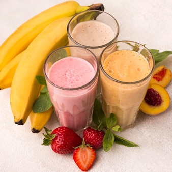 High angle of assortment of milkshakes with fruits