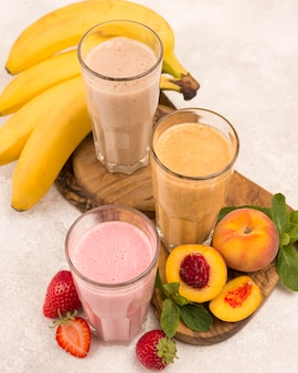 High angle of assortment of milkshakes with peach and banana
