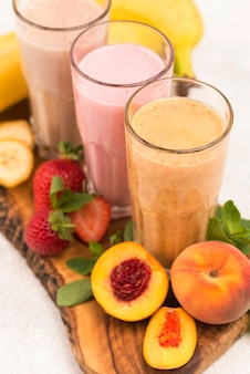 High angle of assortment of milkshakes with peach and strawberry