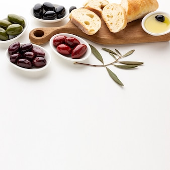 High angle assortment of olives bread slices and olive oil