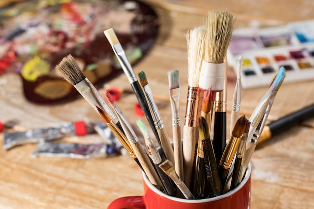 High angle of assortment of paint brushes in mug