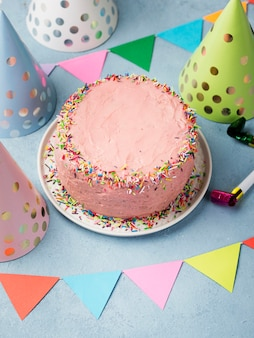 High angle assortment with party hats and pink cake