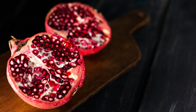 High angle of autumn pomegranate halves with copy space