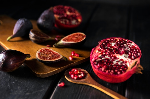 High angle of autumn pomegranates and figs with wooden spoon