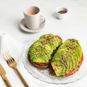 Alto angolo di pane tostato di avocado sul piatto con posate e caffè